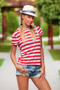 Beautiful sexy girl in shorts and striped t-shirt, in hat, outdoors. Tanned girl in summer Royalty Free Stock Photo