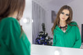 Beautiful sexy girl standing in the mirror with a bright festive make-up in green colors in a beautiful evening dress in the new y Royalty Free Stock Photo