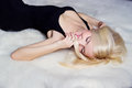 Beautiful sexy happy women blonde with a smile lying on the white carpet in a black dress Royalty Free Stock Photo
