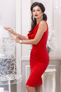 Beautiful sexy luxurious well-groomed young woman in a red slinky dress earrings with diamonds and watches long black hair standin Royalty Free Stock Photo