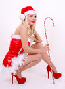 Beautiful sexy Santa girl with candy cane, sitting on white Royalty Free Stock Photos