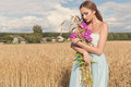 Beautiful sexy slim girl in a blue dress in the field with a bouquet of flowers and ears of corn in his hands at sunset on a sunny Royalty Free Stock Photo