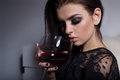 Beautiful sexy sweet girl with full lips bright makeup sitting on the sofa with a glass of wine in a black evening dress Royalty Free Stock Photo