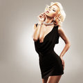 Beautiful sexy white woman in black dress posing at studio Stock Images