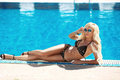 Beautiful sexy woman in black bikini, blond model with sunglasse Royalty Free Stock Photo