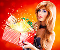 Beautiful sexy woman with a christmas gift photo of magic shining from box studio Stock Image