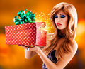 Beautiful sexy woman with a christmas gift photo of magic shining from box studio Royalty Free Stock Photo