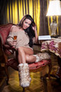 Beautiful sexy woman with glass of wine reading a book sitting on chair portrait long legs posing challenging Royalty Free Stock Photos