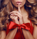 Beautiful sexy woman with long blond curly hair ,red bow on her hands Royalty Free Stock Photo