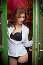 Beautiful sexy woman posing in a green painted door frame. Sexy gorgeous young female with long curly hair opening the door Royalty Free Stock Photo