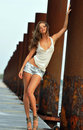 Beautiful sexy woman posing in jeans shorts at rusty boat marina Royalty Free Stock Image