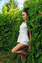 Beautiful sexy woman standing near a green hedgerow outdoors Royalty Free Stock Image