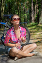 Beautiful sexy woman in sunglasses in the woods drinking water near bicycle Royalty Free Stock Photo