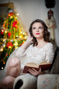 Beautiful sexy woman with xmas tree in background reading a book sitting on chair portrait of a woman reading a book cosy scenery Stock Photo