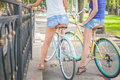 Beautiful sexy women dressed in short shorts travel by bicycle Royalty Free Stock Photo