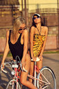 Beautiful sexy women in swimsuits posing near a vintage bike outdoors Stock Photo