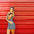 Beautiful sexy young blonde woman posing behind a red wall - cop Royalty Free Stock Photo