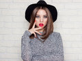 Beautiful sexy young girl in a black hat with red full lips, bright makeup and painted my nails red Royalty Free Stock Photo