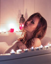 Beautiful sexy young girl with makeup resting in the bath with candles Royalty Free Stock Photo