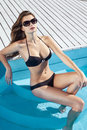 Beautiful sexy young girl with perfect slim figure with long wet hair and bathing suit in fashionable stylish sun glasses sitting Royalty Free Stock Photo