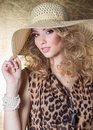 Beautiful sexy young woman in dress leopard bright makeup in the Studio on a gold background in the hat Royalty Free Stock Photo