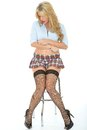 Beautiful sexy young woman wearing a short mini skirt blue shirt alluring with blonde long wavy hair sitting on stool wrapping her Stock Image