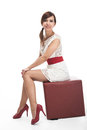 Beautiful shapely model in a miniskirt fashion trendy white with red accessories posing sitting elegantly on square seat Royalty Free Stock Photography