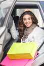 Beautiful shopping addict beautiful young women sitting on the woman back seat of car and holding bags Stock Image