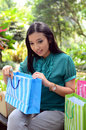 Beautiful shopping woman happy holding shopping bags take rest at garden and smile Stock Photography