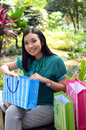 Beautiful shopping woman happy holding shopping bags take rest at garden and smile Royalty Free Stock Image