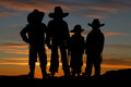 Beautiful silhouette of four young cowboys with a sunset backgro Royalty Free Stock Photo