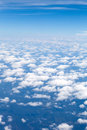 Beautiful skies aerial view of the blue and horizon with fluffy clouds and the earth below Stock Image