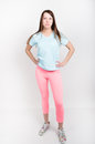 Beautiful slender athletic girl in pink leggings, a blue tank top and colorful Sneakers Royalty Free Stock Photo