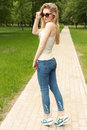 Beautiful slender athletic young sexy girl in sunglasses in jeans and sneakers gleet in the Park summer day Royalty Free Stock Photo