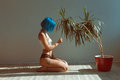 Beautiful slender girl in panties and a T-shirt with blue hair posing on the floor next to a flower in a pot