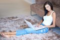 Beautiful slender woman relaxing with her laptop computer on lap as she sits stretched out on the carpet in the living room in Royalty Free Stock Photography
