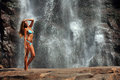Beautiful slim fitness model posing in front of waterfalls Royalty Free Stock Photo