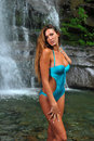Beautiful slim fitness model posing sexy in front of waterfalls wearing one piece swimwear at summer time Stock Image