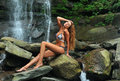 Beautiful slim fitness model posing sexy under waterfalls wearing bikini swimwear at summer time Stock Photography
