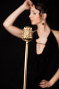 Beautiful slim girl vocalist behind golden vintage microphone Royalty Free Stock Photo