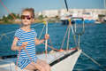 Beautiful slim little girl in a striped t-shirt and sunglasses sitting on board of luxury white yacht in summer cruise Royalty Free Stock Photo