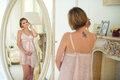 Beautiful slim pregnant girl with a tattoo on shoulder blade looking at herself in the mirror Royalty Free Stock Photo