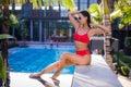 Beautiful slim sexy woman wearing red bikini relax near outdoor water pool on resort Royalty Free Stock Photo
