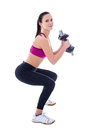 Beautiful slim woman in sports wear squatting with dumbbells iso isolated on white background Stock Photo