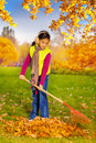 Beautiful small asian girl in with big red rake cleaning grass from fallen leaves the autumn park during daytime Royalty Free Stock Images