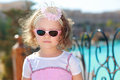 Beautiful small girl in sunglasses on blue sea background Stock Photo