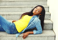 Beautiful smiling african woman wearing a jeans clothes on stairs Royalty Free Stock Photo