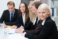 Beautiful smiling blond business woman women attending a meeting with her colleagues at work seated in the foreground of the group Stock Photography