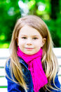 Beautiful smiling blond little girl in the park vertical closeup portrait of a Royalty Free Stock Photos