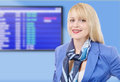 Beautiful smiling blond stewardess, boarding panel on background